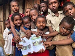 Children holding printed Bible stories