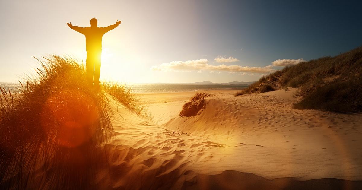 Photo of man worshiping God during a sunrise