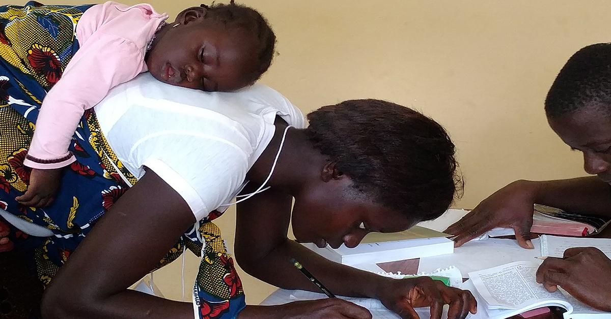 National Bible Translator with sleeping child at work