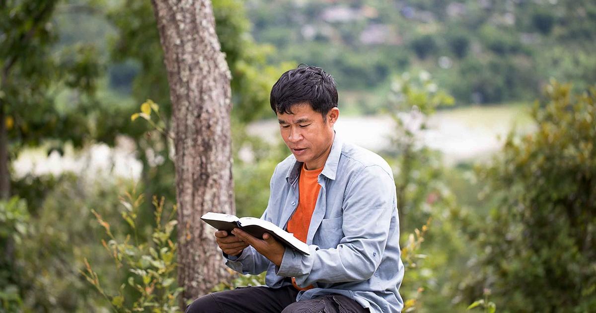asian man reading bible  | MAST Accelerates Bible Translation