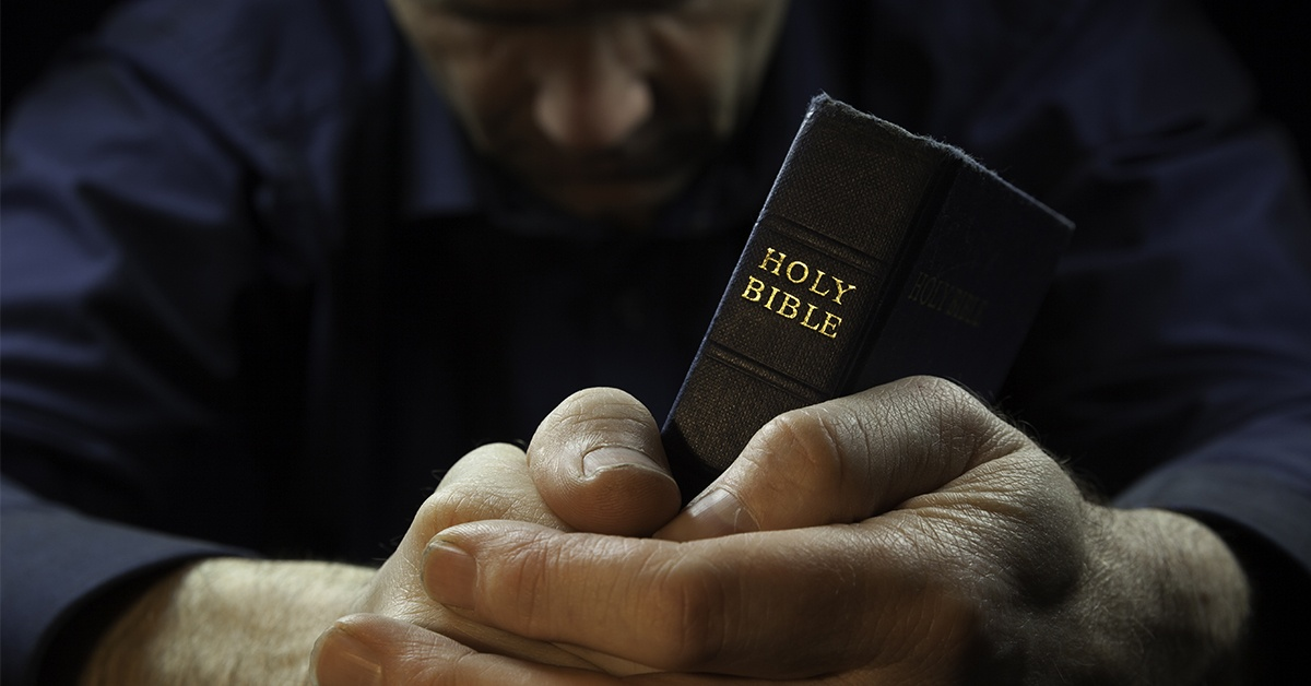 man praying holding Bible | Wycliffe Associates Accelerating Bible Translation
