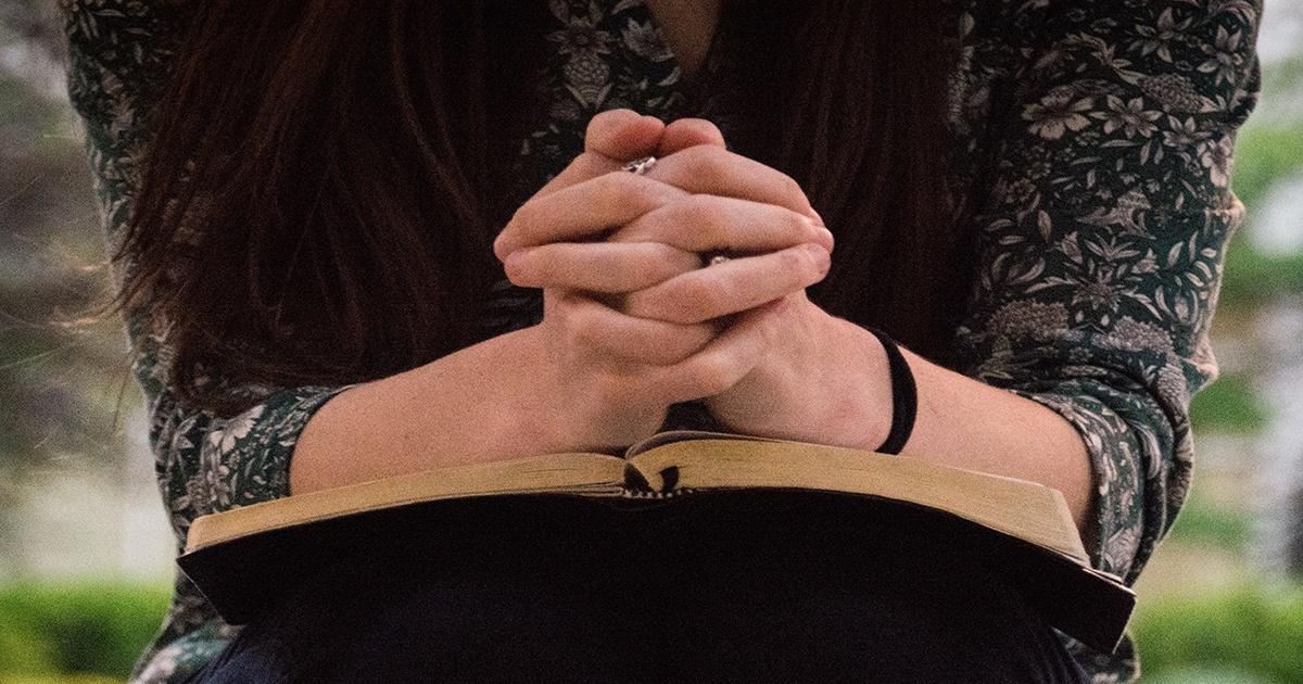 Woman outside praying with Bible | Accelerating Bible Translation