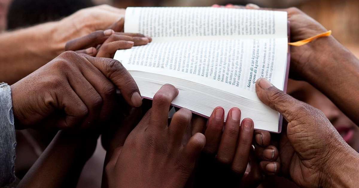 Bible Held by Many Hands